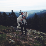 Белая швейцарская овчарка га руках у хозяйки